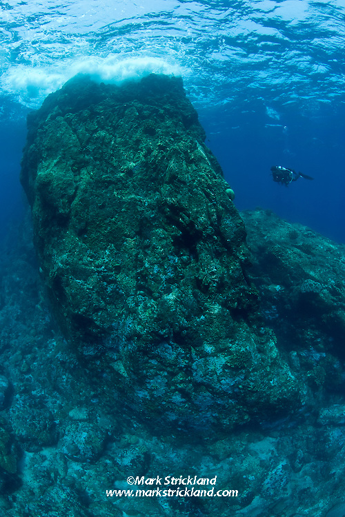 A diver explores amidst rugged topography, typical of many sites at Narcondam Island. Andaman Islands, India, Andaman Sea