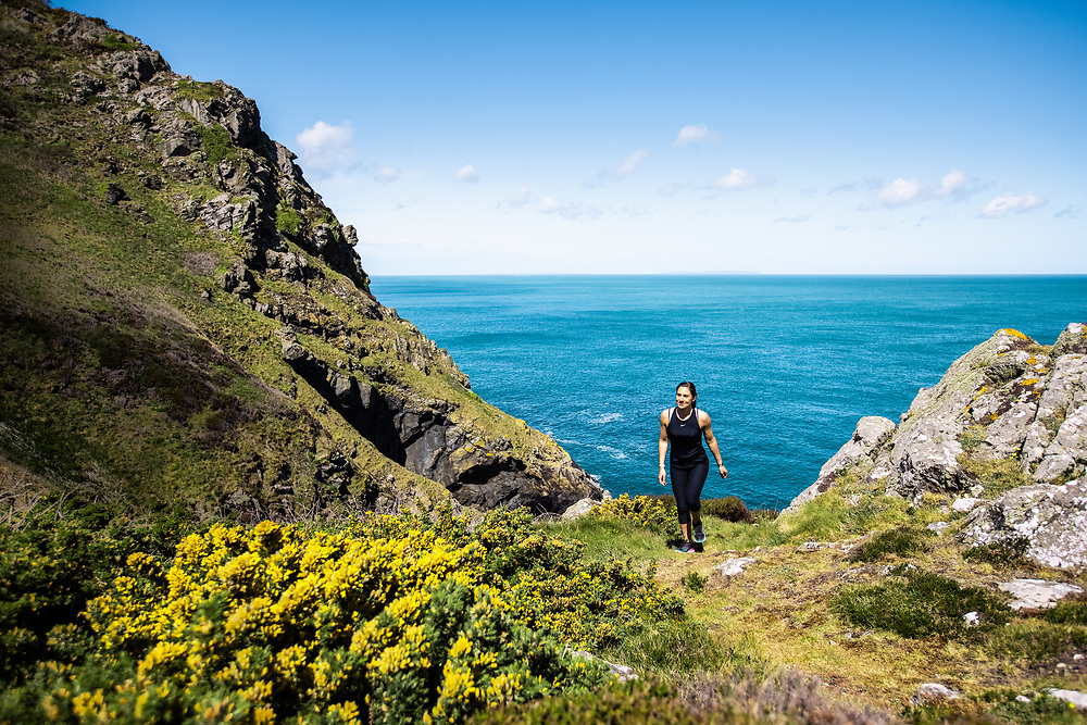 Woman out for a run exploring the headland and coastline along the north of the island in Jersey, CI in Spring