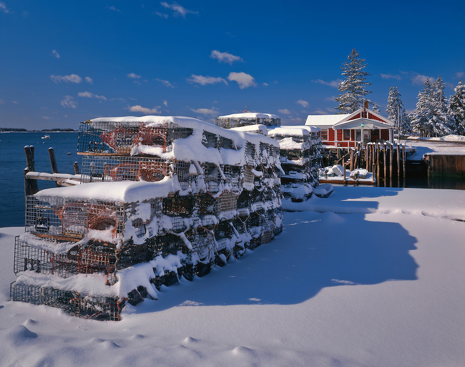 Stacked lobster traps and fish shack in winter, Spruce Head Island, ME