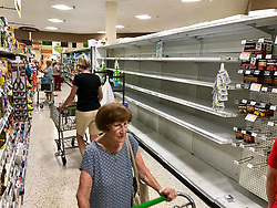 September 5, 2017 - Palm Beach Gardens, Florida, U.S. - Customers walk past empty water isles inside the Publix supermarket in Palm Beach Gardens off of Northlake Boulevard during preparation for hurricane Irma. (Credit Image: © The Palm Beach Post via ZUMA Wire)