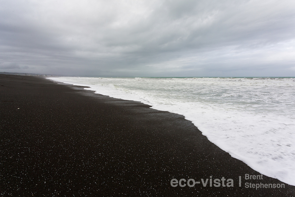 A storm surge rolls in on a black pebble beach, with moody cloudy sky. Westshore Beach, Hawkes Bay, New Zealand. September.