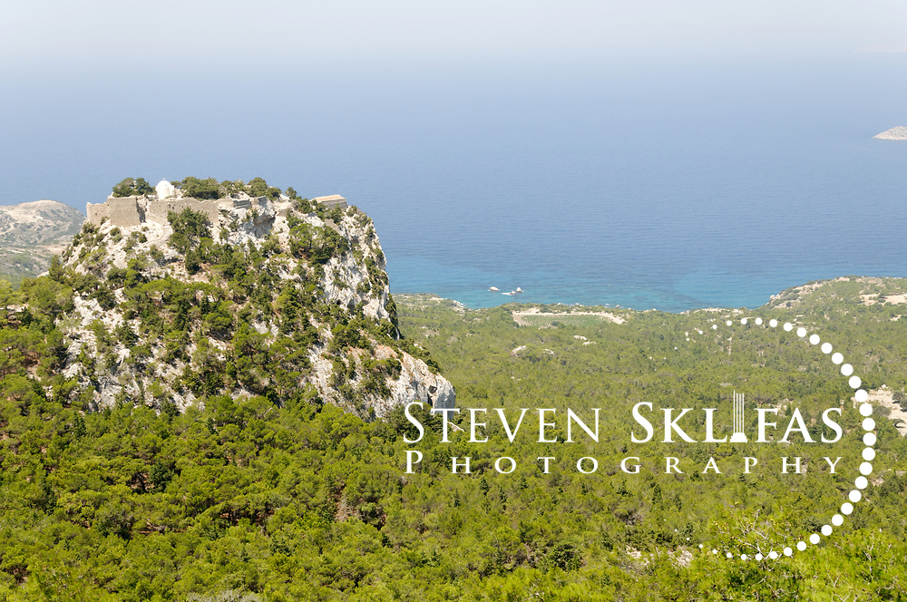 Rhodes. Greece. View of Monolithos, a ruined medieval crusader castle perched atop the enormous crag called Monopetra on the west coast of Rhodes Island. Built by the Knights of St John in 1476, the once impregnable fortress is home to a 15th century whitewashed church of Agios Panteleimon and ruined basilica. Great views of the wild island landscape and wild coastline are on offer and the castle is easily reached by tourists. The island of Rhodes is the largest of the Dodecanese Island group and one of the most popular Greek Islands.