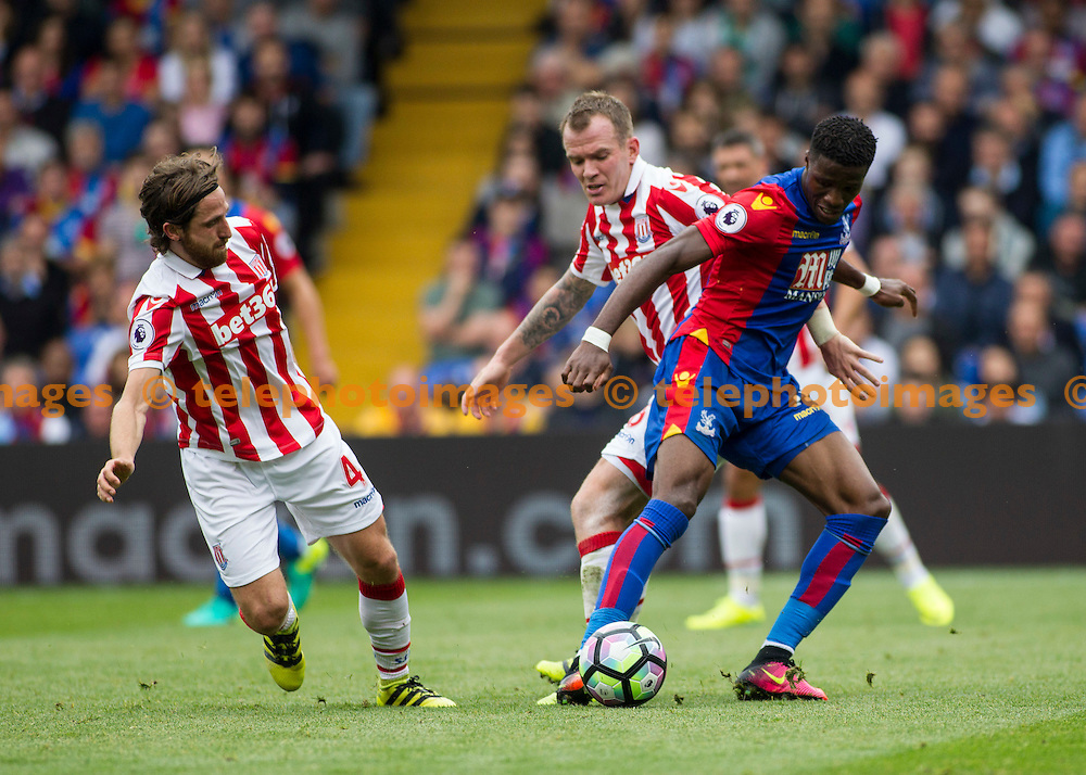 Wilfried Zaha fends off a defensive challenge during the Premier League match between Crystal Palace and Stoke City at Selhurst Park in London. September 18, 2016.<br /> Jack Beard / Telephoto Images<br /> +44 7967 642437