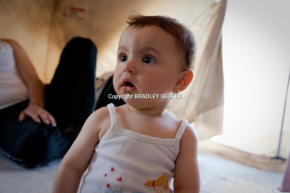 A young Syrian girl sits in a tent with her father in southern Turkey. The recent massacres of women and children in villages in Syria have caused an international outcry. Yayladagi, Hatay, Turkey. 11/06/2012