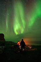 Sitting around an campfire with northern lights - aurora borealis in the sky overhead, Unstad, Vestvågøy, Lofoten Islands, Norway