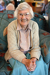 Cheerful looking elderly woman sitting with her hands on her lap,