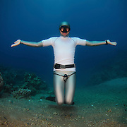 Freediver underwater in the Red Sea. Photographed in Aqaba, Jordan. Model Release Available. Freediving (or free-diving) is a form of underwater diving that does not involve the use of scuba gear or other external breathing devices, but rather relies on a diver's ability to hold his or her breath until resurfacing.
