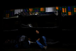 Men who were detained by US Border Patrol and returned to Mexico after a failed attempt to cross the border wait for lights out in a shelter.  These men have little or no money and will spend the night in Nogales while they decide whether to return home or make another attempt at crossing.