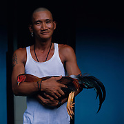 THE PHILIPPINES (Manila). 2009. Bernard Osorio, 34, with his game cock before the cockfighting at the La Loma Cockpit, La Loma, Manila. Photo Tim Clayton <br /> <br /> Cockfighting, or Sabong as it is know in the Philippines is big business, a multi billion dollar industry, overshadowing Basketball as the number one sport in the country. It is estimated over 5 million Roosters will fight in the smalltime pits and full-blown arenas in a calendar year. TV stations are devoted to the sport where fights can be seen every night of the week while The Philippine economy benefits by more than $1 billion a year from breeding farms employment, selling feed and drugs and of course betting on the fights...As one of the worlds oldest spectator sports dating back 6000 years in Persia (now Iran) and first mentioned in fourth century Greek Texts. It is still practiced in many countries today, particularly in south and Central America and parts of Asia. Cockfighting is now illegal in the USA after Louisiana becoming the final state to outlaw cockfighting in August this year. This has led to an influx of American breeders into the Philippines with these breeders supplying most of the best fighting cocks, with prices for quality blood lines selling from PHP 8000 pesos (US $160) to as high as PHP 120,000 Pesos (US $2400)..