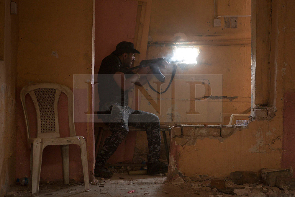 Licensed to London News Pictures. 01/04/2017. Mosul, Iraq. An Iraqi Federal Police officer fires at Islamic State fighters, around 175 metres away, from his position in West Mosul, Iraq, today (01/04/2017). Iraqi forces continue to fight house to house as they push further into West Mosul. Iraqi forces are now advancing on the city's old districts where Islamic State fighters still hold out. Photo credit: Matt Cetti-Roberts/LNP