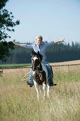 Mid adult woman riding galloping horse without holding reins in the farm, Bavaria, Germany
