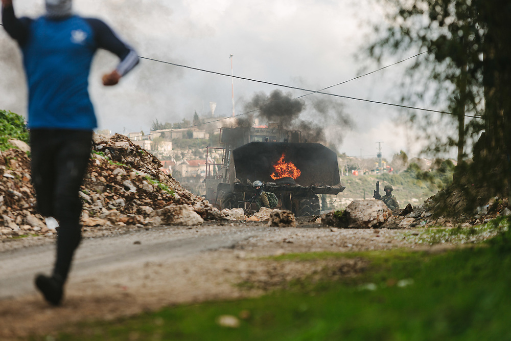 Palestinians run away from an Israeli bulldozer during a weekly demonstration against the expropriation of Palestinian land by Israel and against the closure of the main road leading to Nablus, in the Palestinian village of Kufr Qaddum, West Bank, on February 21, 2020. The Israeli settlement of Kdumim, is seen in the background.