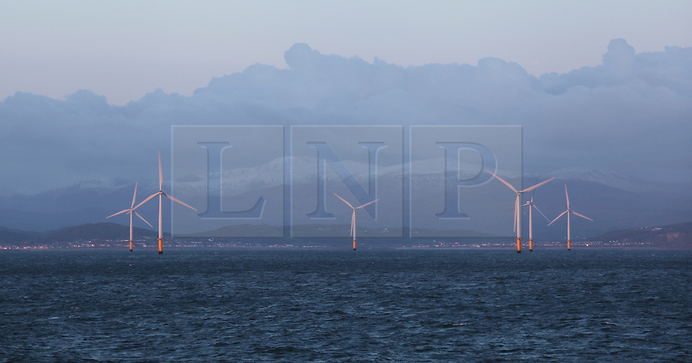 © Licensed to London News Pictures. 22/03/2014. North Wales, UK. The rising sun reflects off the turbines of the Rhyl Flats Offshore Wind Farm off the coast of North Wales this morning, 22nd March 2014. The snow capped hills of Snowdonia National Park can be seen in the distance. Photo credit : Rob Arnold/LNP
