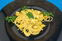 yellow black spaghetti presentation: curry spaghetti on black dish close-up from above