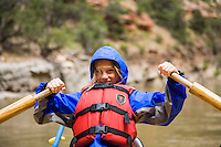 Young girl learning to row while on a multi-day whitewater raft trip on the Yampa River which flows through Dinosaur National Monument in northeastern Utah.