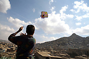 Ehsan, 13, the eldest son of Noor Agha, flies a kite next to his house, Kabul, Afghanistan, Saturday, March, 10, 2007. Noor Agha is a renowned kite maker who made kites for the movie makers of the best-selling novel, The Kite Runner, which will be distributed by Dreamworks and Paramount Vantage in Nov. this year. Noor Agha's wives, using their special glue, help him produce enough kites to please the clients' needs. Some of his children can also make their own kites with plastic bags and bamboo sticks. As the Afghan New Year's Day (Nawruz) approaching on March 21, the finger tips of Noor Agha's family got busier for mass production.