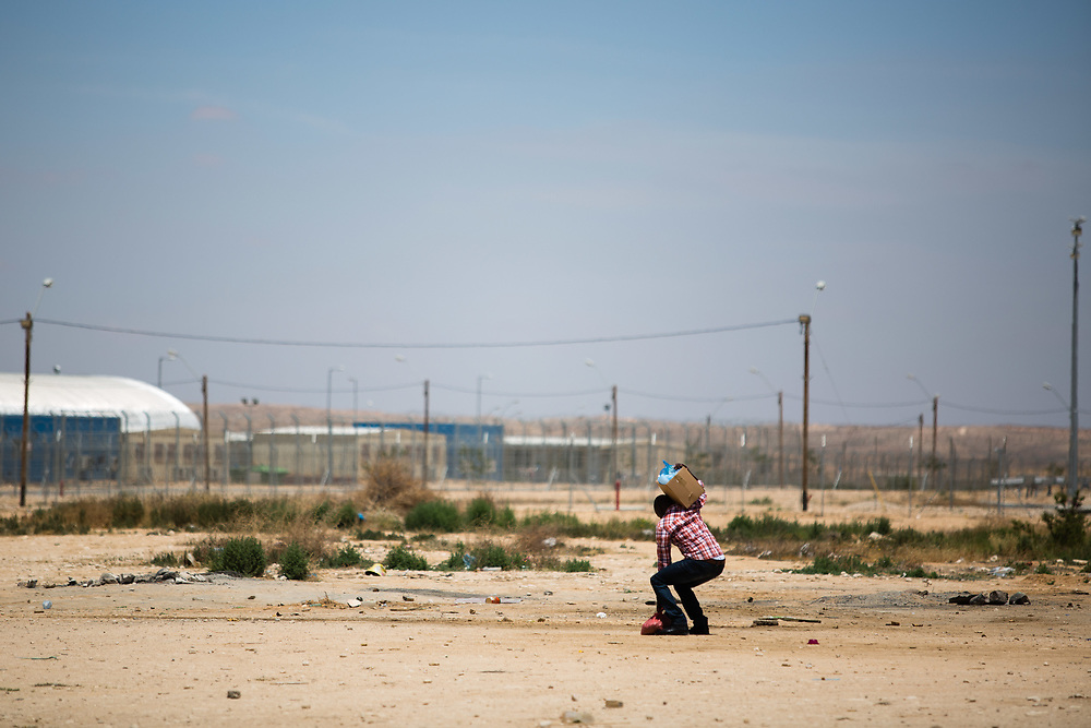 An African asylum seeker is seen carrying food and supplies outside Holot detention center, where African migrants are being held in the Negev Desert, southern Israel, on May 4, 2015.