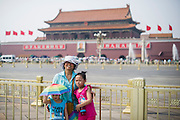 A Chinese family takes a picture protecting from the sun's rays in Tiananmen Square in Beijing, China, July 20, 2014. <br /> <br /> Pale skin has historically been prized as beautiful in China, and the concept is widespread in other Asian countries. Besides health topics, beauty is one of the main reasons that makes protection from the sun's rays so important. <br /> <br /> © Giorgio Perottino