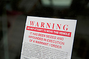 Warning to not move a vehicle is placed onto the window of a car. Due to not being moved for some considerable time, the warning is placed in advance of the car being impounded. London, UK.