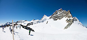 """Jungfraujoch """"Top of Europe"""" is the highest railway station in Europe (3454 meters elevation). Here, visitors can admire a high-Alpine wonderland from platforms atop the Aletsch Glacier or carved inside, in the Ice Palace. Jungfraujoch is a col at 3466 m between the peaks of Jungfrau and Mönch in the Bernese Alps, on the boundary between the cantons of Bern and Valais, halfway between Interlaken and Fiesch, in Switzerland, Europe. Engineering this dramatic cog-wheel railway required 16 years (1898-1912) to carve through the Eiger and Mönch for 7 kilometers (4.3 mi), with gradients of up to 25%. Kleine Scheidegg entry station can be reached by trains from Grindelwald and Lauterbrunnen. The ride from Kleine Scheidegg to Jungfraujoch takes 50 minutes including stops at Eigerwand and Eismeer viewing portals. Downhill return takes just 35 minutes. Jungfraujoch hosts an important station of Global Atmosphere Watch (GAW), plus the Sphinx Observatory for astronomy at 3571 meters or 11,716 feet. The Swiss Alps Jungfrau-Aletsch region is honored as a UNESCO World Heritage Site. This image was stitched from multiple overlapping photos."""