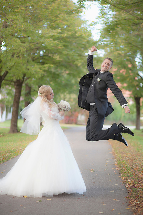 Bride holding bouquet and groom jumping in tree avenue, Ammersee, Upper Bavaria, Bavaria, Germany