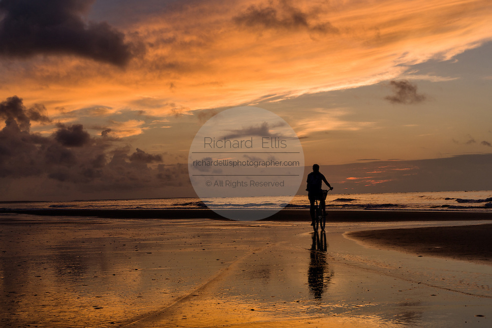 Silhouette of a bicyclist at sunrise on Isle of Palms beach at Wild Dunes near Charleston, South Carolina.