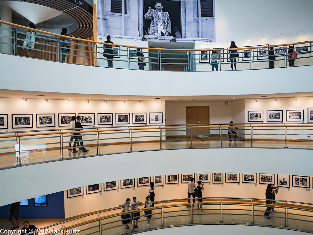 """06 NOVEMBER 2016 - BANGKOK, THAILAND: People walk through a photo exhibit honoring Bhumibol Adulyadej, the late King of Thailand at the Bangkok Art and Culture Centre. The Royal Photographic Society of Thailand with the Bangkok Art and Culture Centre and Thai Beverage Public Company Limited are hosting a photography exhibition to commemorate the late Thai King Bhumibol Adulyadej. The """"In Remembrance of His Majesty King Bhumibol Adulyadej"""" Photography Exhibition is dsiplaying 89 photographs by 89 photographers honoring King Bhumibol Adulyadej's legacy. The King was an avid photographer was usually seen with a camera in his hands. The exhibition will be on display until 27 November 2016 on the Curved Walls on the 3rd - 5th floor, Bangkok Art and Culture Centre.     PHOTO BY JACK KURTZ"""