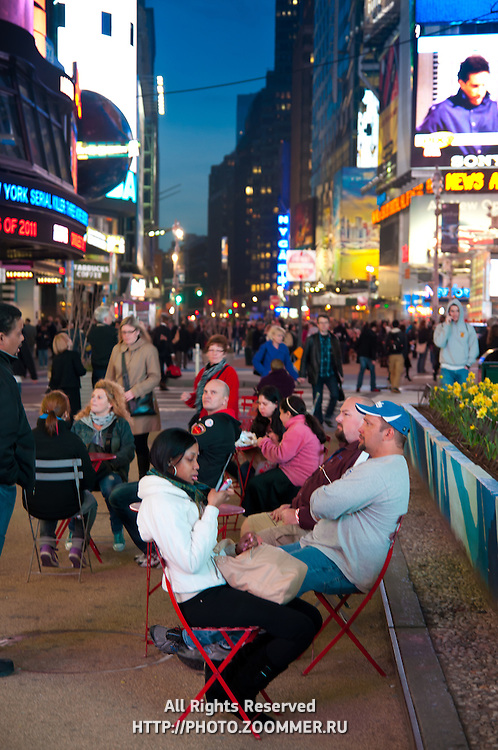 People sitting in chairs in street cafe on Times Square, New York City, USA