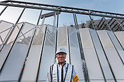 A security guard stands in front of a gate at the National Stadium, Shinjuku, Tokyo, Japan. Friday March 6th 2015. Large scale demolition work officially began, March 5th to remove  the old stadium, which was the venue for the 1964 Olympics, after many delays. Construction of the new Olympic stadium for the 2020 games is scheduled to begin in October 2015