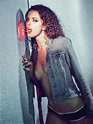 Woman wearing panties and a dungaree jacket appears to want to lick a light switch decrotated with pink fuzzy fabric.