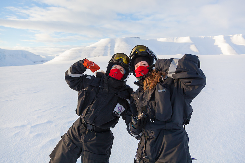 UNIS students Désirée Treichler and Sofie Vej Ugelvig play it up for the camera on Rabotbreen, Svalbard, on a class field trip by snowmobile to Tunabreen.