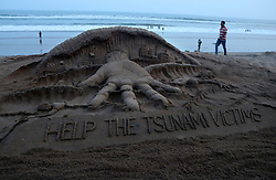 September 30, 2018 - Bhubaneswar, Odisha, India - A sand sculpture creating by Indian sand artist Sudarshan Pattnaik on the Bay of Bengal beach at Puri asks for help for Indonesia Tsunami victims. (Credit Image: © NurPhoto/ZUMA Press)