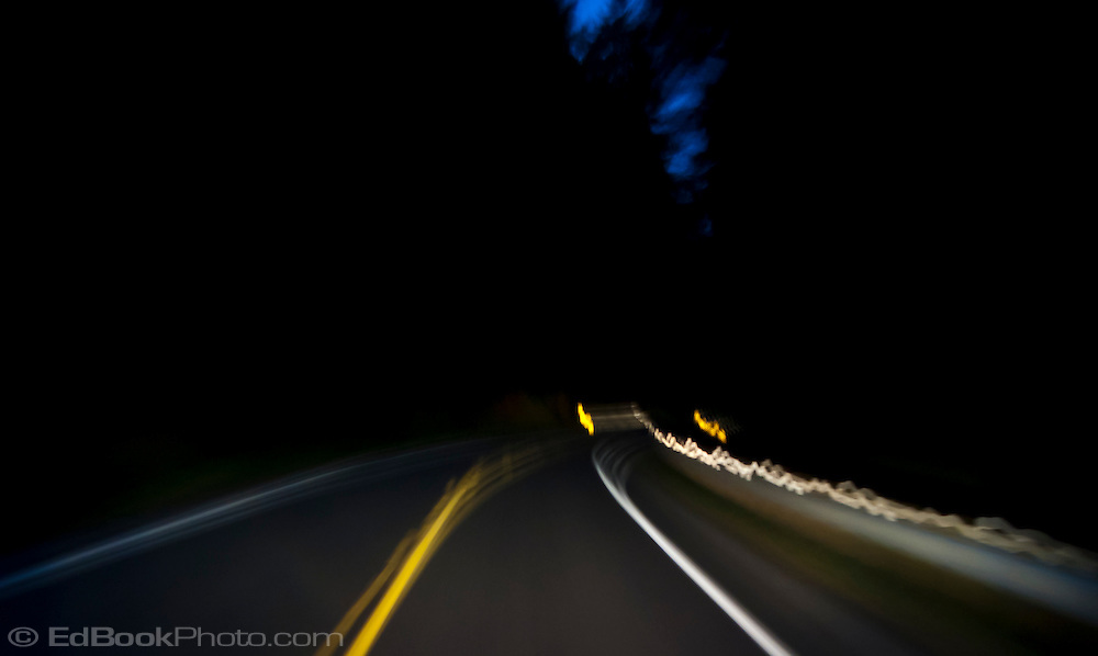 an abstract image of a curve in the road in the forest at night