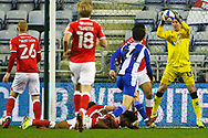 Charlton Athletic goalkeeper Ben Amos (13) saves the shot from Wigan Athletic midfielder Alex Perry (24) during the EFL Sky Bet League 1 match between Wigan Athletic and Charlton Athletic at the DW Stadium, Wigan, England on 2 March 2021.
