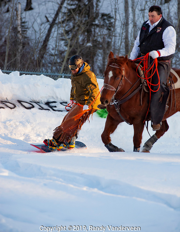 Photo Randy Vanderveen<br /> 2019-03-08<br /> Grande Prairie, Alberta<br /> Dan Boorse stays close behind the hooves of a charging Thumber ridden by Jason Skene at Thunder in the Pines at Evergreen Park Friday evening. The inaugural skijoring event, which saw someone on skis or a snowboard pulled around by a horse or horse and rider on a closed course proved a popular event at the Foster's Peace Country Ag Classic for both spectators and participants.