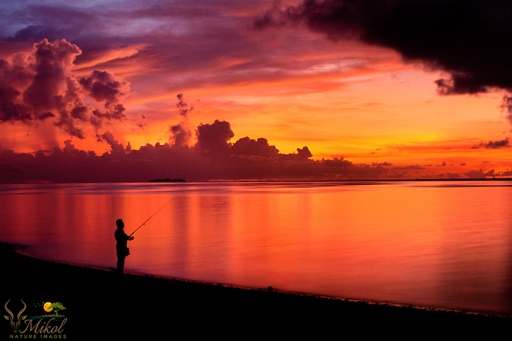 Fishing at sunsest with clouds lit by setting sun and reflecting in water.