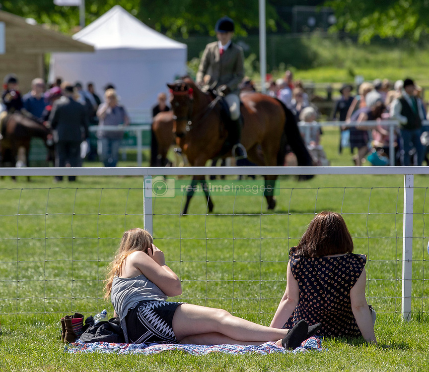 Spectators sunbath as they watch the showing during day one of the Royal Windsor Horse Show at Windsor Castle, Berkshire.