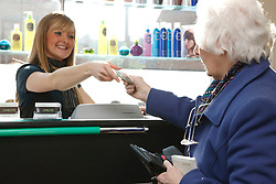 Elderly customer paying for hairdressing appointment.