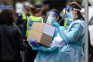Healthcare workers wearing full PPE are seen carrying boxes and documents before they enter the main tower at 120 Racecourse Road amid a full and total lockdown of 9 housing commission high rise towers in North Melbourne and Flemington during COVID-19 on 5 July, 2020 in Melbourne, Australia. After 108 new cases where uncovered overnight, the Premier Daniel Andrews announced on July 4 that effective at midnight last night, two more suburbs have been added to the suburb by suburb lockdown being Flemington and North Melbourne. Further to that, nine high rise public housing buildings in these suburbs have been placed under hard lockdown for a minimum of five days, effective immediately.  Residents in these towers will not be allowed to leave their units for any reason. Police will be stationed at every entry and exit point, every level, and they will also surround these locations preventing any movement in, or out. There is a total of 1354 units and over 3000 residents living in these buildings including the states most vulnerable people. These new restrictions will remain in place for fourteen days with fears of further lockdowns to come. The Government have stressed that if Victorians do not follow the basic COVIDSafe rules, the whole state will go back in to lockdown. (Image by Dave Hewison/ Speed Media)