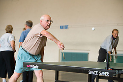 Older man playing table tennis in a community centre sports hall,