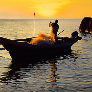 Silhouette of fisherman with nets on his boat at the dusk (ZooMMER Travel Photography)