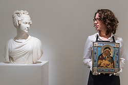 """© Licensed to London News Pictures. 25/11/2016. London, UK. A technician views a marble bust of """"Empress Alexandra Feodorovna"""" (est. 15-20k), whilst holding """"A Fabergé gem-set silver-gilt and enamel icon of the Yaroslavskaya Mother of God"""" (est. GBP 30-50k), at the preview of artworks from Sotheby's upcoming Russian sales in New Bond Street, where over three hundred works spanning several centuries will be offered. Photo credit : Stephen Chung/LNP"""