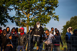© London News Pictures. Calais, France. A group of African immigrants watch police before attempting to access the Eurotunnel complex.  Migrants attempting to reach the UK via the Eurotunnel at Calais in France. The situation has reached crisis point, which French police over run by attempts to cross the border. Photo credit: Ben Cawthra /LNP