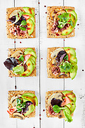 Canapes with mushrooms avocado salad prosciutto on bread crouton with seeds white wooden background top view shot<br /> <br /> Sold exclusively through Stockfood.com<br /> See the Licensor link below.