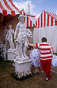 A woman in red striped top looks at home next marquees of a similar pattern and colour as he leans against the nude male figure of a garden ornament at the Chelsea Flower Show, the annual event held by the Royal Horticultural Society (RHS) in London. Her friend bends down and the statue with a hand on his leg has a smile on his face.