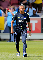 Brighton Manager Chris Hughton makes his way to the dug out before kick off during a pre season friendly match at The Cherry Red Records Stadium, Kingston Upon Thames.
