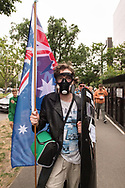 A protester wearing gas mask with a riot shield and an Australian flag marches down St Kilda Road during the Sack Daniel Andrews Protest as it moved from Fawkner Park. Parts of the community are looking to hold the Victorian Premier accountable for the failings of his government that led to more than 800 deaths during the Coronavirus crisis. Victoria has recorded 36 days Covid free as pressure mounts on the Premier Daniel Andrews to relax all remaining restrictions. (Photo by Michael Currie/Speed Media)