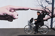 A salaryman (make office worker) on a bicycle rides past a construction site wall with photos of pointing fingers on it. Otemachi, Tokyo, Japan. Friday March 4th 2016