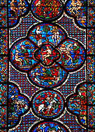 Medieval stained glass Window of the Gothic Cathedral of Chartres, France - dedicated to the lGood Samaritan . Central panel shows Adam dwelling in Paradise, below - At the inn, the Samaritan nurses the injured man back to health, left - God breathing life into Adam, above - God warning Adam and Eve not to eat from the tree of knowledge, right - God creates Eve out of Adam's rib . bottom central oval panel - The Samaritan leading the Pilgrim to an inn, left of this - A Samaritan binds the injured man's wounds, right of centre - An innkeeper welcoming the Samaritan.  A UNESCO World Heritage Site..