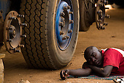 A driver rests on the ground beside his truck as he waits for spare parts for repairs near Notse, Togo on Thursday October 2, 2008.